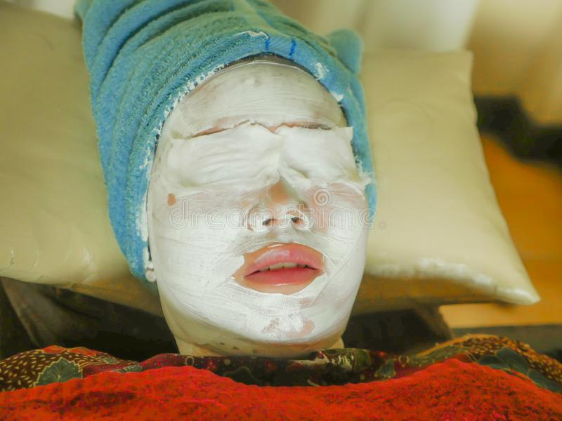 Young woman with towel wrapped on head and face mask lying on bed at wellness spa receiving beauty facial treatment in well being. Skin care and healthy stock images