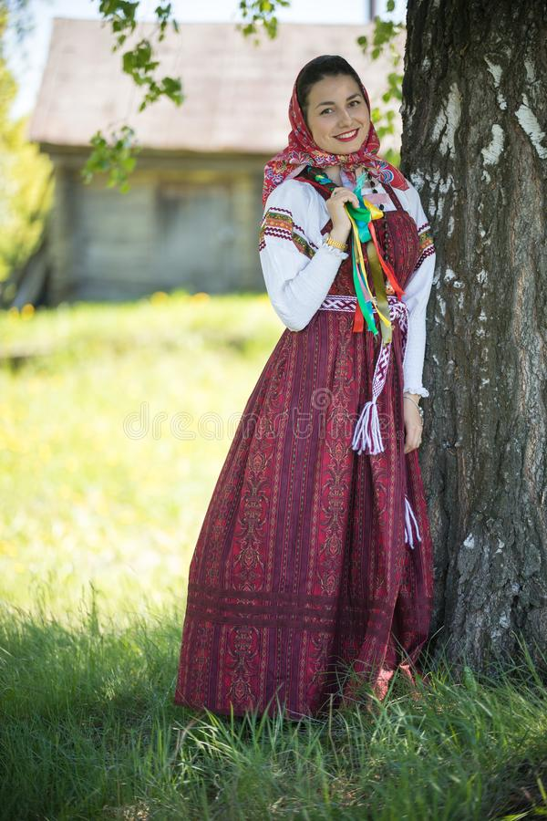 Young woman in traditional russian clothes standing under a tree and holding her pigtail. Vertical shot royalty free stock images