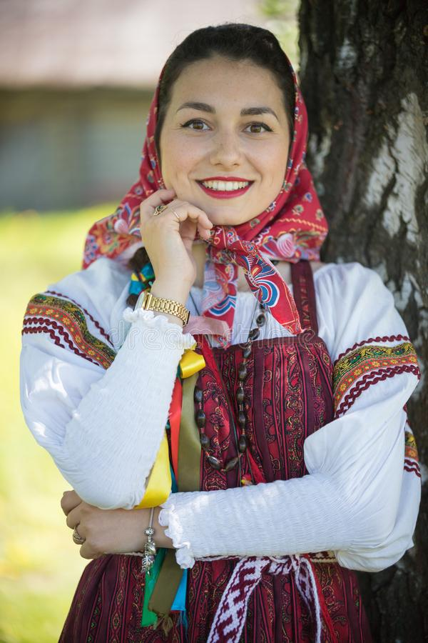 Young woman in traditional russian clothes standing under a tree and holds hand at face - looking to camera. Vertical shot royalty free stock photos