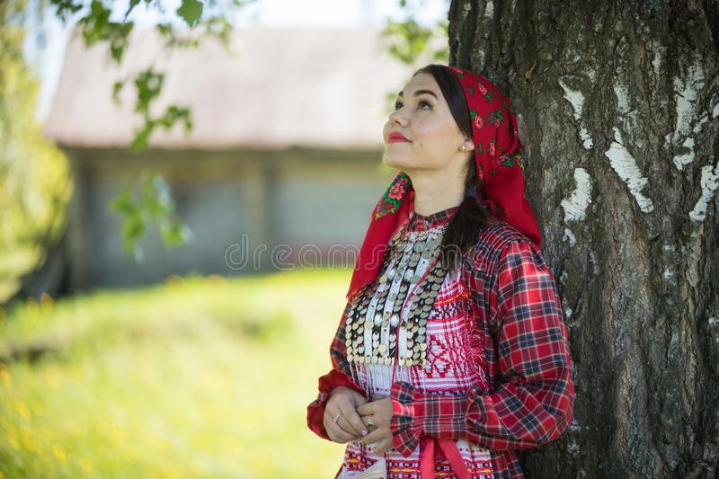 Young woman in traditional russian clothes standing under a tree and looking up. Middle shot stock image