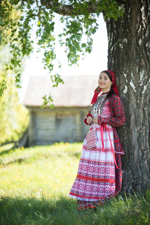 Young woman in traditional russian clothes standing under a tree and posing for a photo. Vertical shot royalty free stock photography