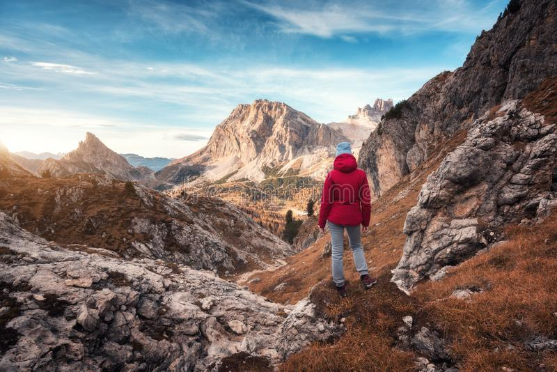 Young woman on the trail looking on high mountain peak at sunset. In Dolomites, Italy. Autumn landscape with girl, path, rocks, sky with clouds at colorful royalty free stock photo