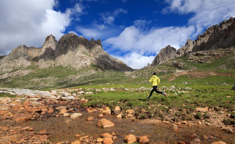 Runner running at high altitude mountains. Young woman trail runner running at high altitude mountains stock photography