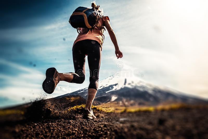 Woman hiker. Young woman, trail running athlete runs on the trail with loose ground and volcano on the background. Tilt shift effect applied stock image