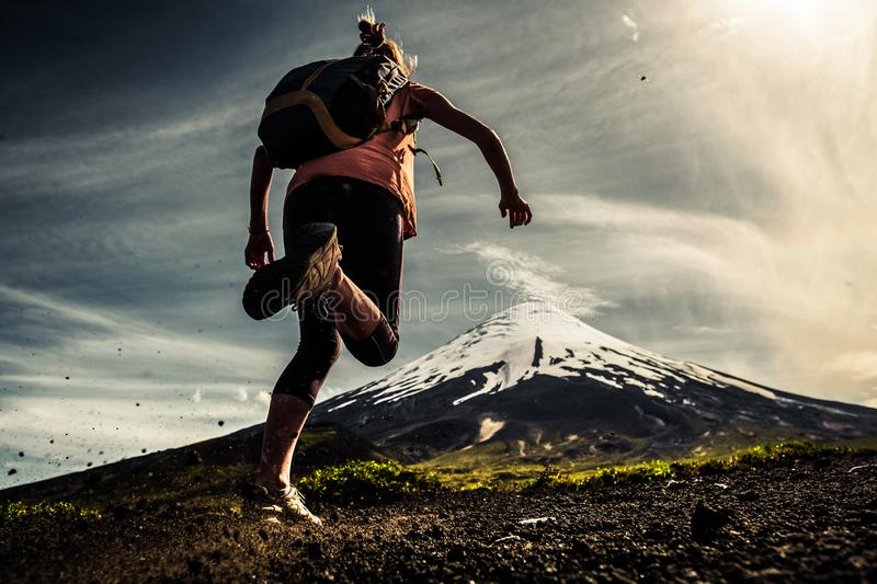 Woman hiker. Young woman, trail running athlete runs on the trail with loose ground and volcano on the background stock image