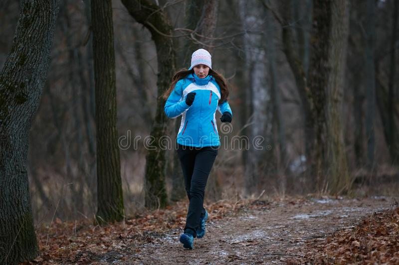 Young woman on trail running in winter park royalty free stock photo