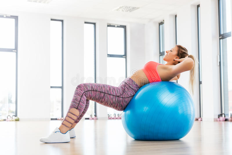 Young woman training with fitball at fitness club. royalty free stock photography
