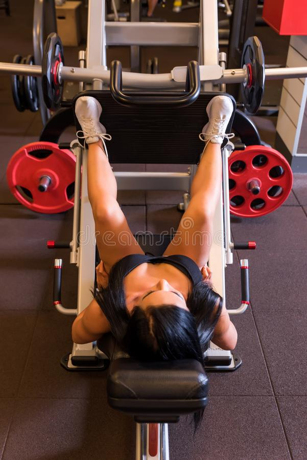 A young woman training her legs on a weight lifting machine. A beautiful young woman training her legs on a weight lifting machine in the Gym.r royalty free stock photography