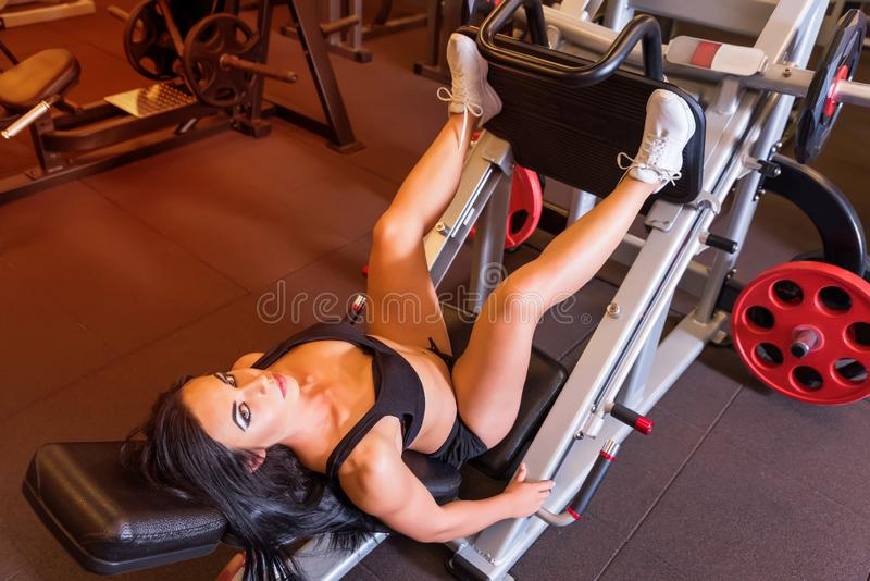 A young woman training her legs on a weight lifting machine. A beautiful young woman training her legs on a weight lifting machine in the Gym.r royalty free stock photo