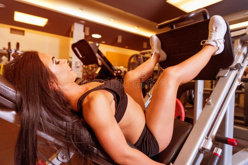 A young woman training her legs on a weight lifting machine. A beautiful young woman training her legs on a weight lifting machine in the Gym.r royalty free stock photos