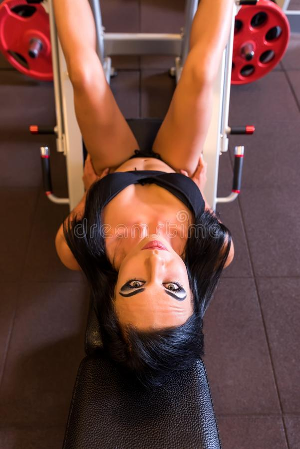 A young woman training her legs on a weight lifting machine. A beautiful young woman training her legs on a weight lifting machine in the Gym.r stock photography