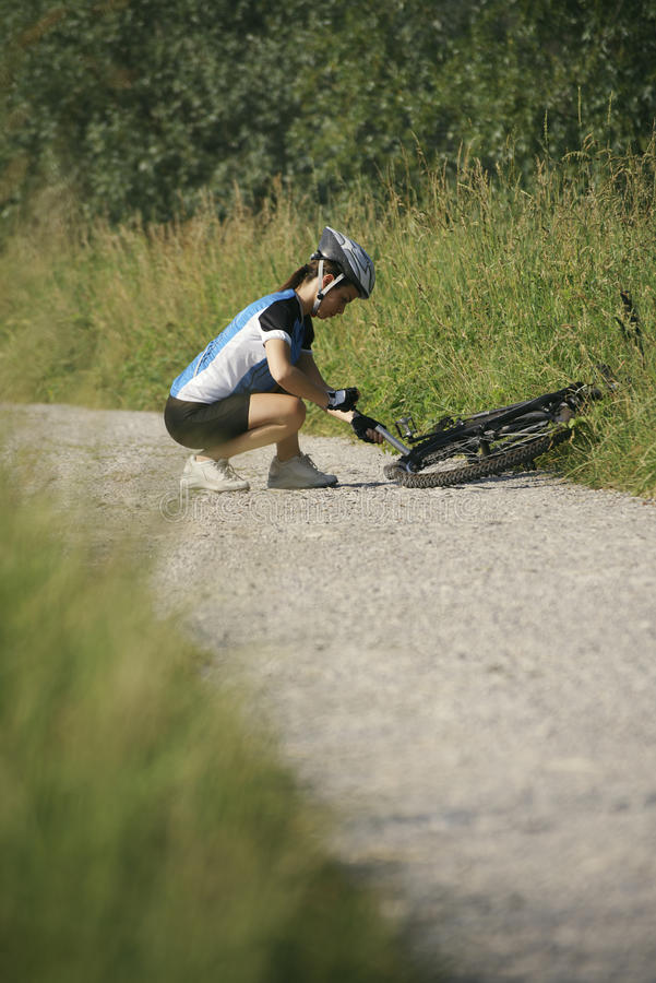 Young woman training on mountain bike and cycling in park. Young woman training on mountain bike and repairing flat tyre on track in countryside stock photo