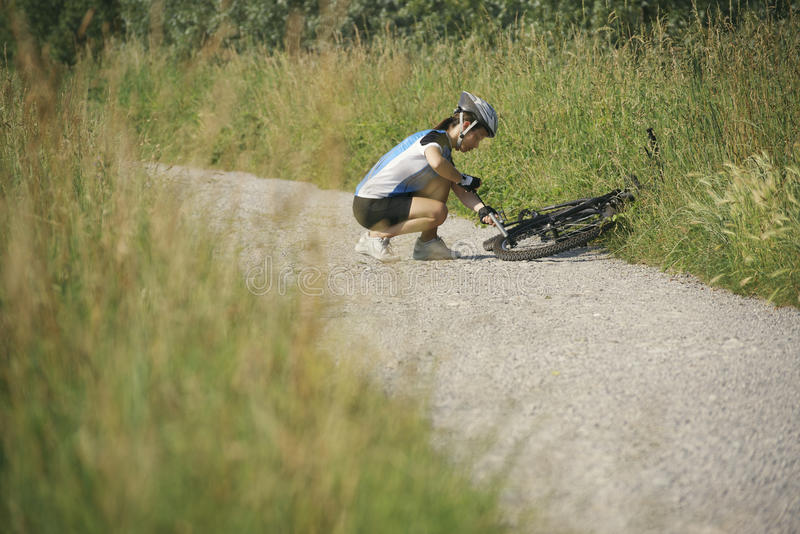 Young woman training on mountain bike and cycling in park. Young woman training on mountain bike and repairing flat tyre on track in countryside royalty free stock image