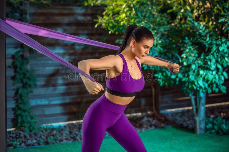 Young woman is training with rubber bands outdoors. Healthy active lifestyle concept. girl doing fitness in the park royalty free stock photography