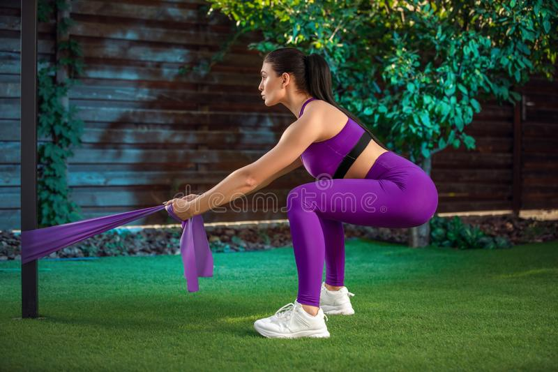 Young woman is training with rubber bands outdoors. Healthy active lifestyle concept. girl doing fitness in the park stock photos