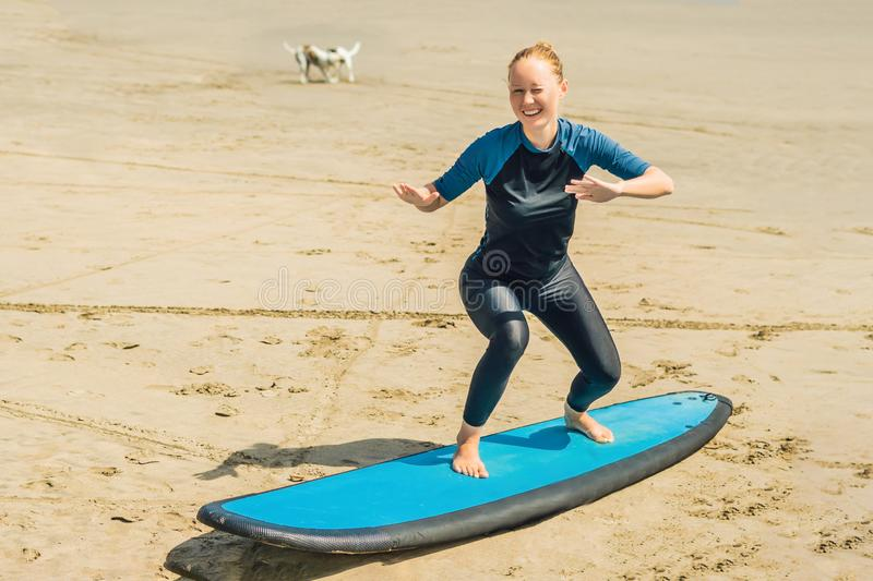 Young woman is training to stand on the surf before the first surfing lesson.  stock photo