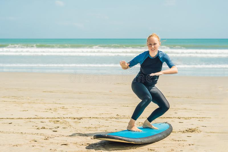 Young woman is training to stand on the surf before the first surfing lesson.  stock photography