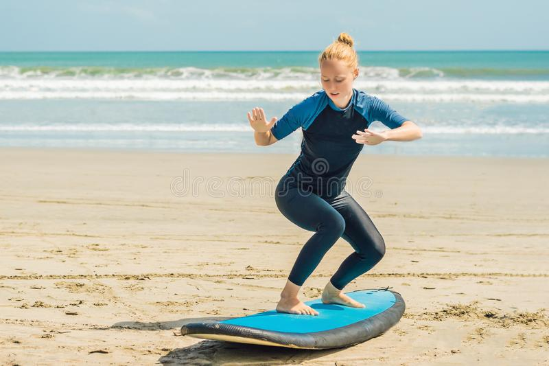 Young woman is training to stand on the surf before the first surfing lesson stock photography