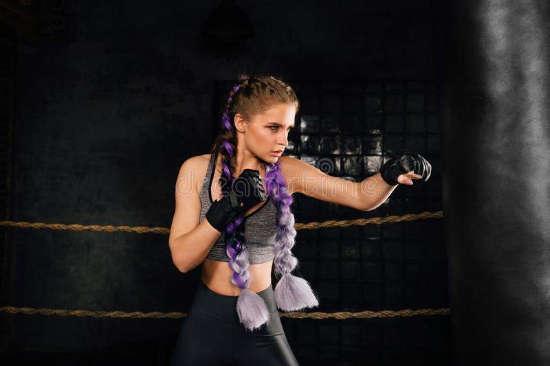 Young woman trains in boxing ring with heavy punching bag. stock image