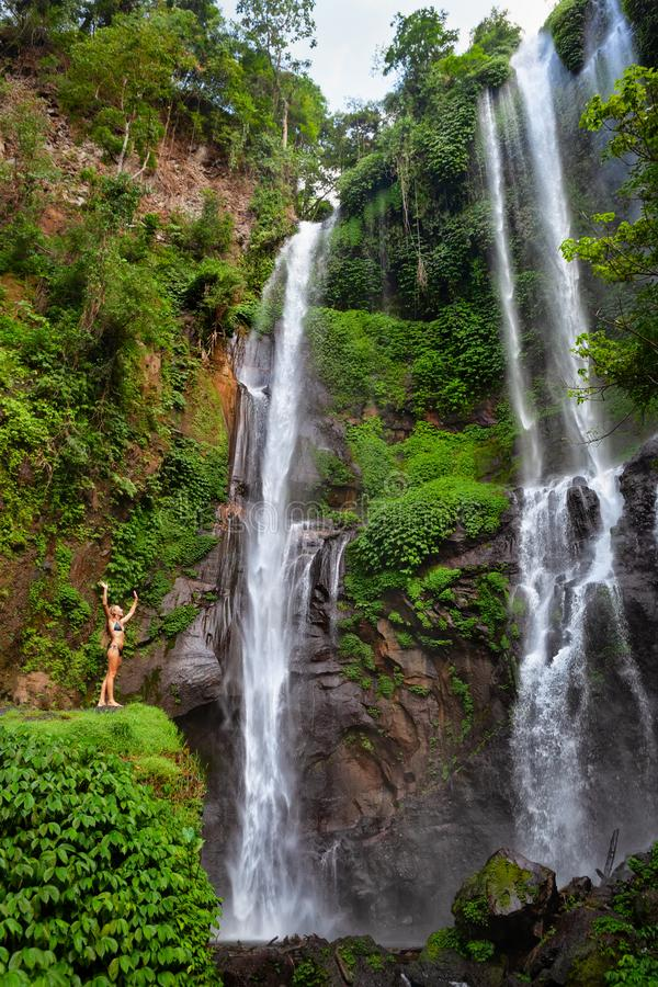 Woman stand under Sekumpul waterfall, see on falling water. Young woman travel in Bali rainforest. Happy girl enjoy jungle nature. Stand in natural pool under stock photos