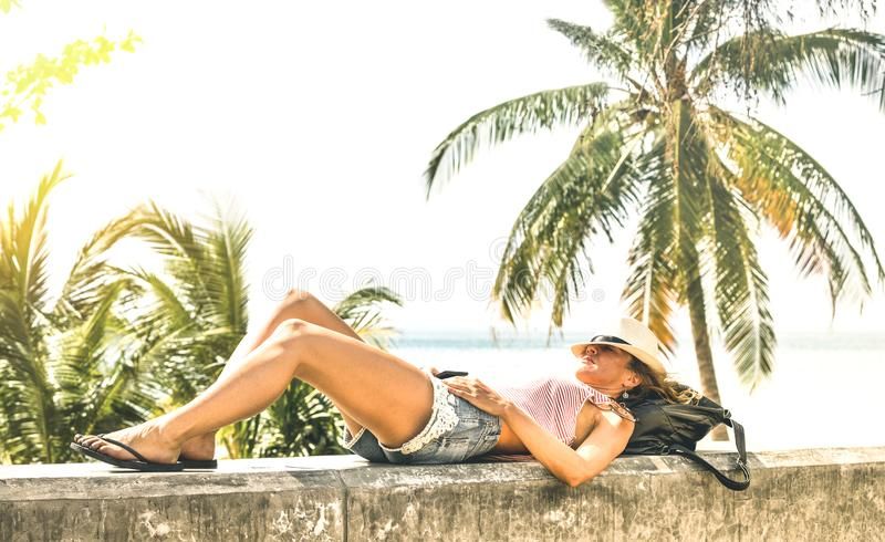 Young woman travel influencer relaxing on stone wall at Phuket beach promenade - Wanderlust vacation concept with adventure girl. Tourist wanderer on trip stock photo