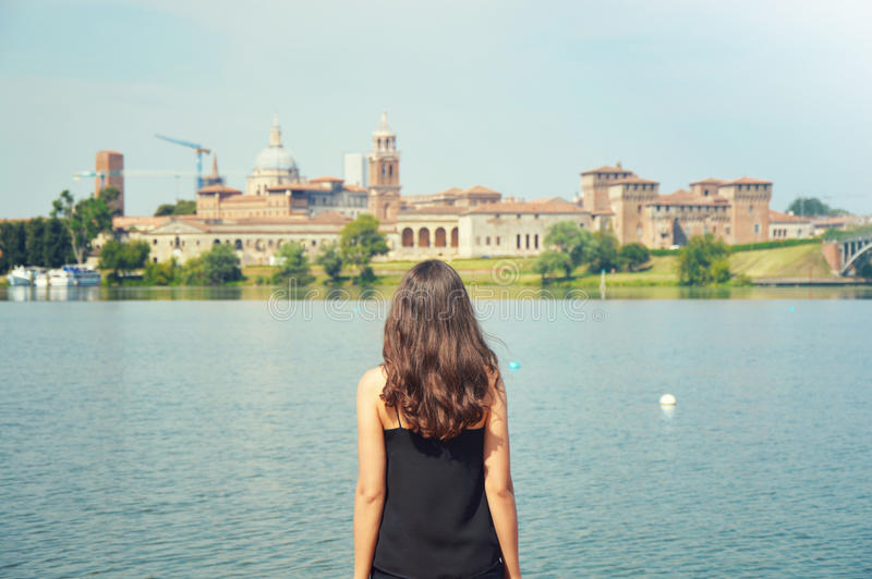 Young woman travel to Europe. Happy Tourist in Mantua looking at cityscape. Cheerful brunette girl traveler enjoy italian landscap stock photography