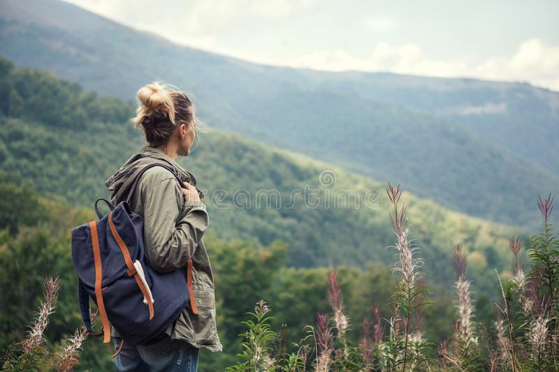 Young woman traveler with backpack hiking in the mountains royalty free stock photos
