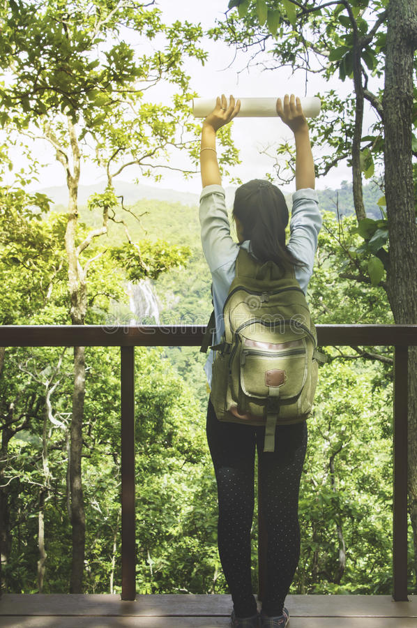 Young Woman Traveler with backpack relaxing outdoor with waterfall and rocky mountains on background Summer vacations. stock photos