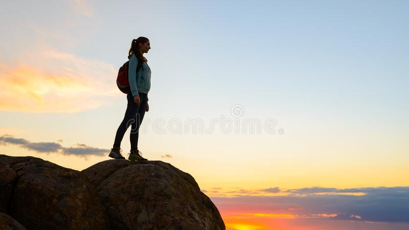 Young Woman Traveler with Backpack Standing on the Top of the Rock at Summer Sunset. Travel and Adventure Concept. stock images