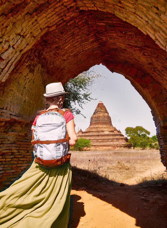 Young woman traveler with a backpack walking through the Old Bagan looking the ancient Buddhist stupas. Burma royalty free stock photos