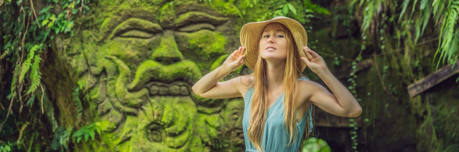 Young woman traveler in a Balinese garden overgrown with moss. Travel to Bali concept BANNER, LONG FORMAT. Young woman traveler in a Balinese garden overgrown royalty free stock photo