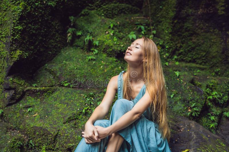 Young woman traveler in a Balinese garden overgrown with moss. Travel to Bali concept stock photo