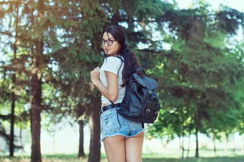 Young woman traveler with backpack standing alone in forest. Hipster girl in sunny woods royalty free stock photo