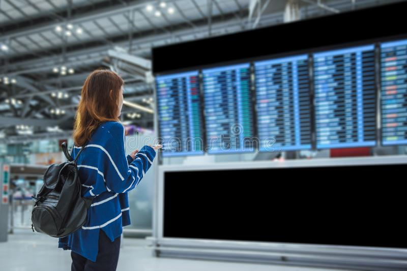Young woman traveler in international airport looking at the flight information board stock photo