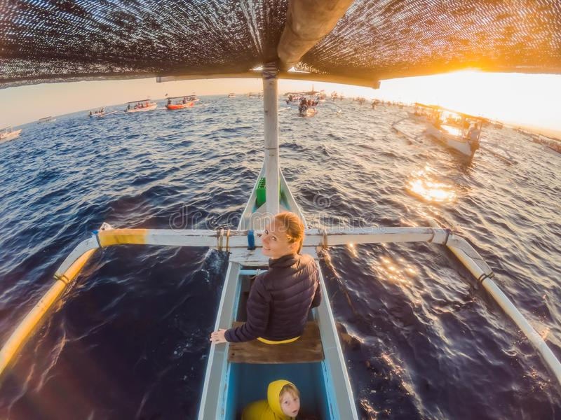 Young woman traveler meets dawn in the sea on a boat.  royalty free stock images
