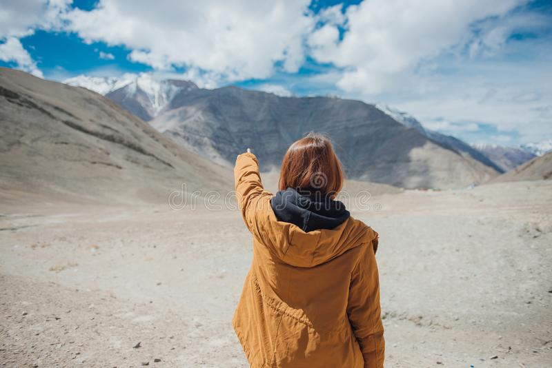 Young woman traveler pointing to the sky enjoy the beautiful view at mountain in Leh. stock photography