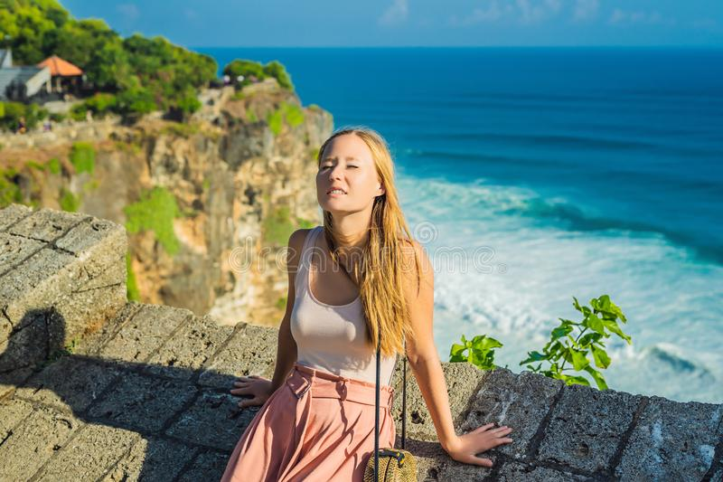 Young woman traveler in Pura Luhur Uluwatu temple, Bali, Indonesia. Amazing landscape - cliff with blue sky and sea.  royalty free stock photos