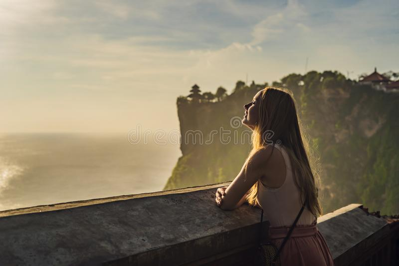 Young woman traveler in Pura Luhur Uluwatu temple, Bali, Indonesia. Amazing landscape - cliff with blue sky and sea.  stock image