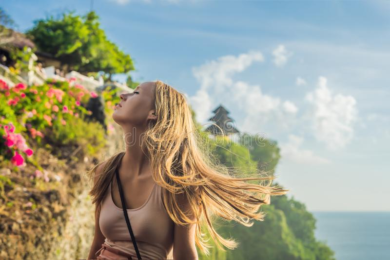 Young woman traveler in Pura Luhur Uluwatu temple, Bali, Indonesia. Amazing landscape - cliff with blue sky and sea.  royalty free stock photography