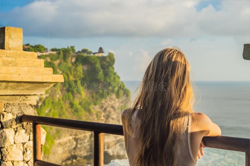 Young woman traveler in Pura Luhur Uluwatu temple, Bali, Indonesia. Amazing landscape - cliff with blue sky and sea.  stock photo