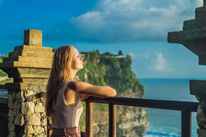 Young woman traveler in Pura Luhur Uluwatu temple, Bali, Indonesia. Amazing landscape - cliff with blue sky and sea.  royalty free stock photo