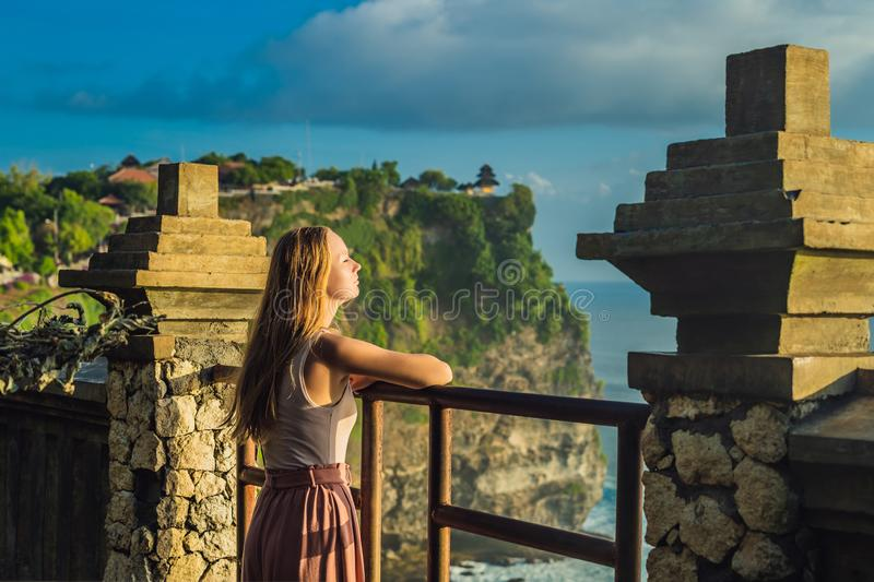 Young woman traveler in Pura Luhur Uluwatu temple, Bali, Indonesia. Amazing landscape - cliff with blue sky and sea.  stock photos