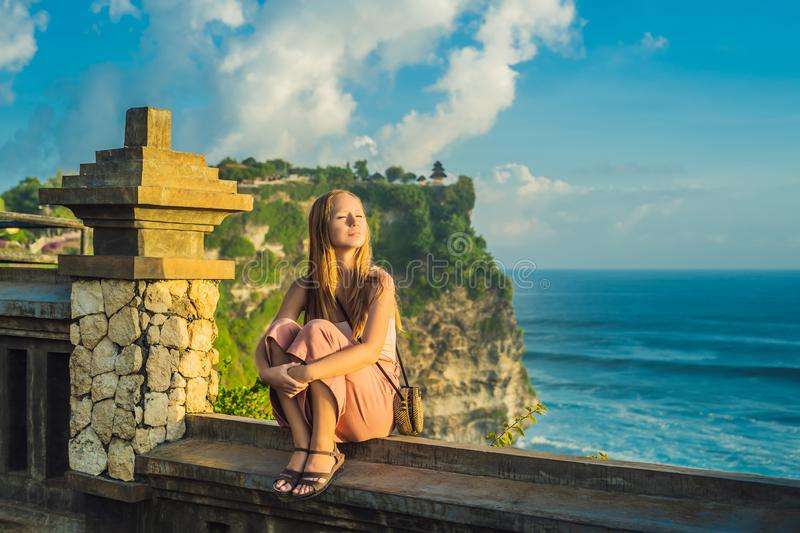 Young woman traveler in Pura Luhur Uluwatu temple, Bali, Indonesia. Amazing landscape - cliff with blue sky and sea.  stock photography