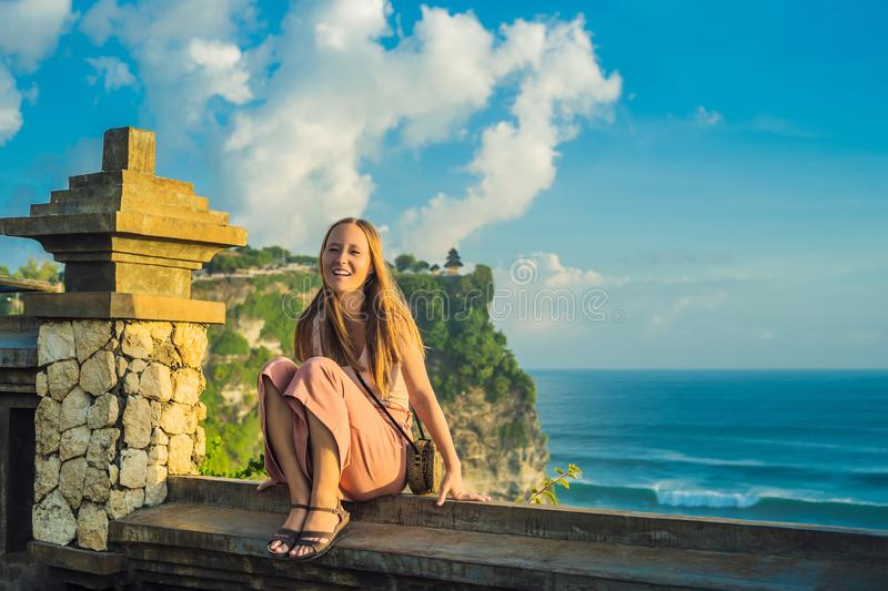 Young woman traveler in Pura Luhur Uluwatu temple, Bali, Indonesia. Amazing landscape - cliff with blue sky and sea.  royalty free stock image