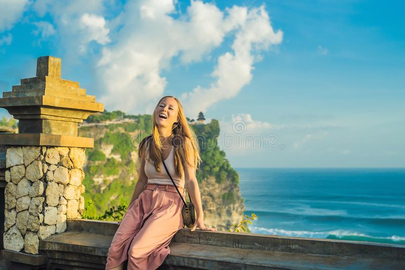 Young woman traveler in Pura Luhur Uluwatu temple, Bali, Indonesia. Amazing landscape - cliff with blue sky and sea.  stock images