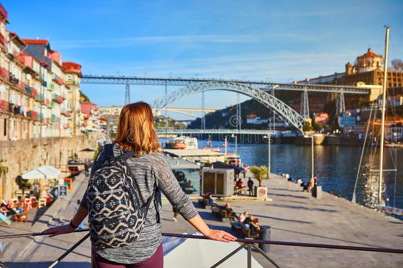 Young woman traveler standing back enjoying beautiful cityscape view on Douro river, bridge and boats during the morning light in royalty free stock photos