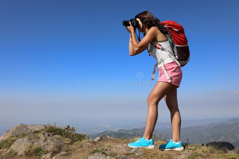 Young woman traveler taking photo on mountain peak royalty free stock photo