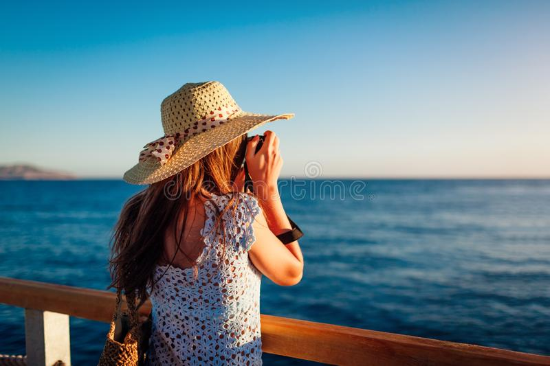 Young woman traveler taking photos of sea landscape on pier using camera. Summer fashion royalty free stock photography