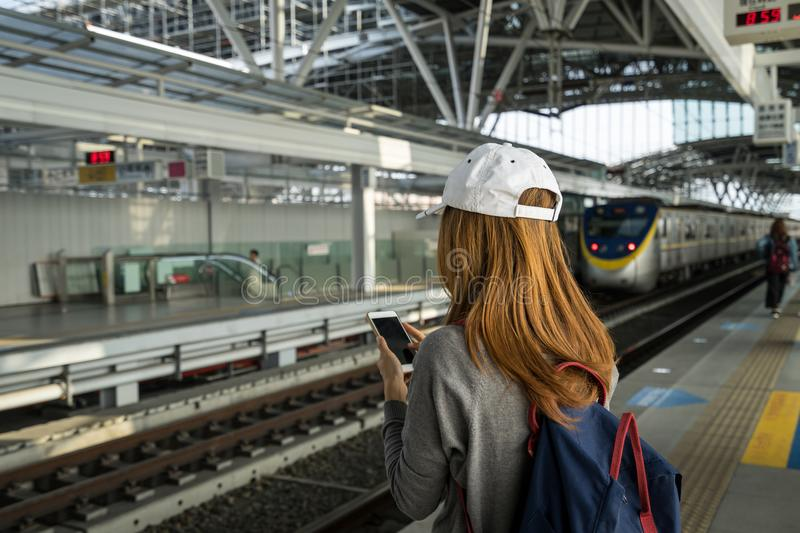 Young woman traveler using travel app in smart phone stock photography