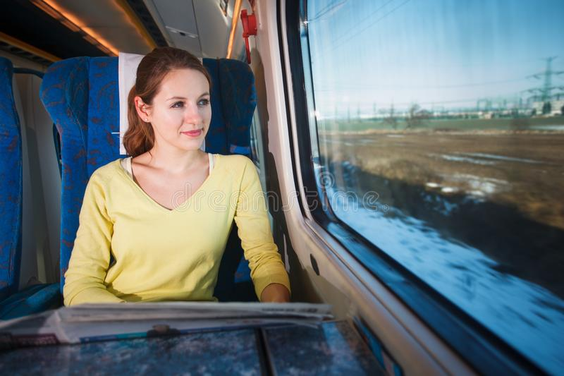 Young woman traveling by fast moving train. Looking at the motion blurred landscape passing by royalty free stock photos